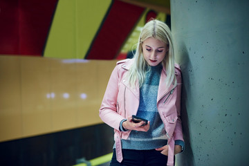 Young woman waiting in underground station looking at smartphone