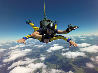 Portrait of tandem skydivers free falling above clouds and landscape