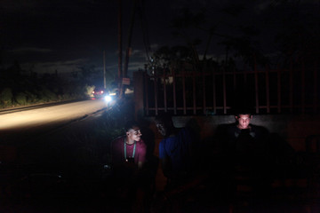 People use their mobile phones near a mobile phone antenna tower as cars drive in the dark in Dorado