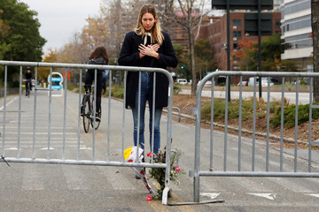 Caroline Ventura looks down at flowers she laid for victims of Tuesday's attack outside a police barricade on the bike path next to West Street in New York City