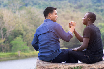 Concept of best friends,African man and asian man  shaking hands with happy and smile.