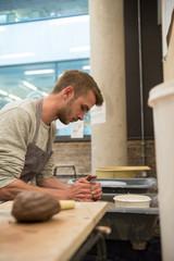 Man in art studio using pottery wheel