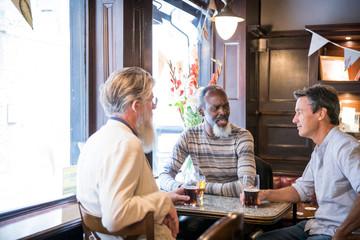 Three mature men, sitting together in pub, talking