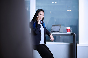 Businesswoman using smartphone, making telephone call, smiling