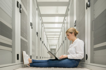 Young woman in data centre, sitting on floor, using laptop