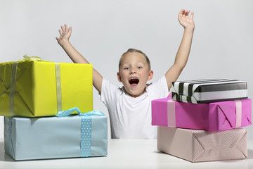 little boy with five colored presents is happy in front of white background with open mouth and hands up in the air