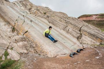 Woman sliding down rock slide, Sacsayhuaman, Cusco, Peru, South America