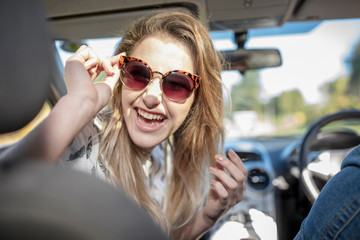 Young woman in car, looking over shoulder, laughing