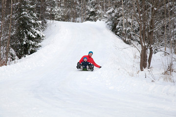 Man and son tobogganing down hill in snow covered forest