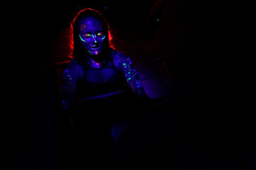 Woman wearing neon paint on her face and arms takes part in a yoga class in Ciudad Juarez
