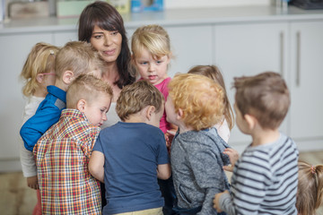 Teacher in classroom, surrounded by young children