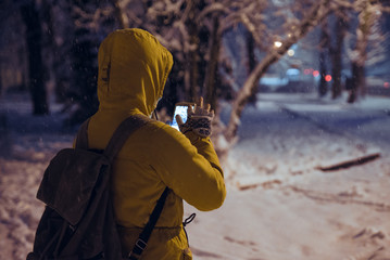 young woman standing at night winter city park in the evening and taking picture