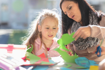 Mid adult woman helping young girl with crafting activity