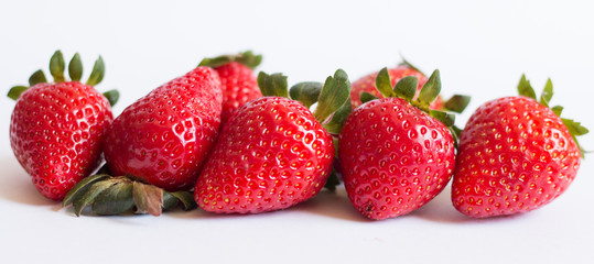 Ripe strawberries lined horizontally with white background