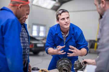 Car mechanic team discussing car part in repair garage