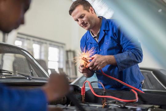 Car mechanics testing car engine in repair garage