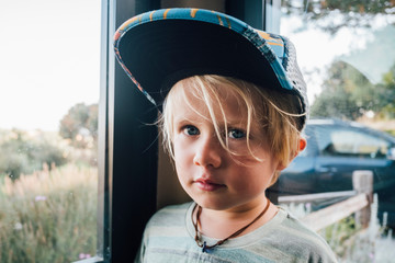 Portrait of blond haired boy wearing baseball cap by window