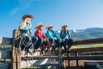 Cowboys and cowgirls on fence, looking away, Enterprise, Oregon, United States, North America
