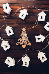 Christmas decoration made of small linked metallic houses with a christmas tree hole and light inside and a christmas decoration in the middle over a rusty wooden background, concept for home holiday