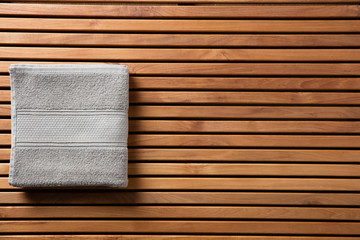 Concept for shower or spa with towel over wooden board