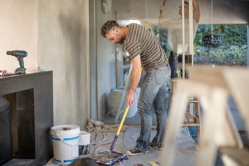 Two men in unfurnished home, decorating using paint roller