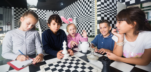 five children play in quest room in chess style