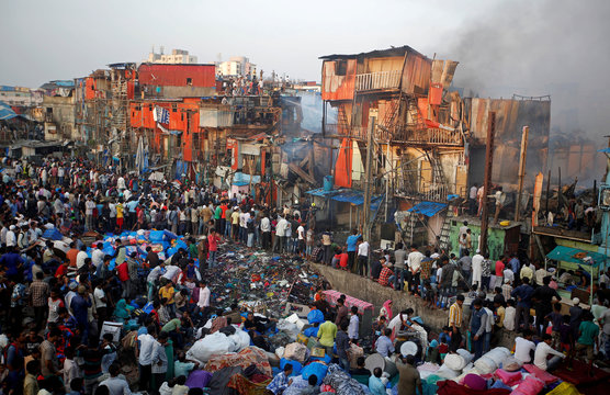 People watch as rescue workers and firemen try to douse a fire which broke out in a slum area in Mumbai
