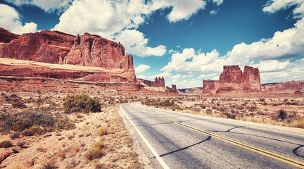 Vintage toned panoramic picture of a scenic road, travel concept picture, Arches National Park in Utah, USA.