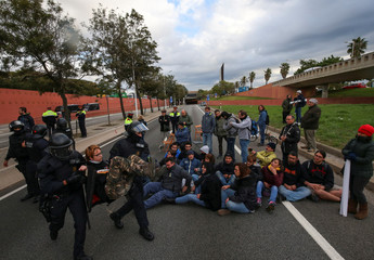 Police remove a protestor who was part of a group of protestors blocking a ring road in Barcelona during a partial regional strike in Barcelona