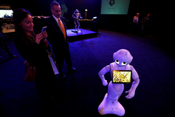 A visitor takes pictures of a robot during an exhibition on 'Neom', a new business and industrial city, in Riyadh