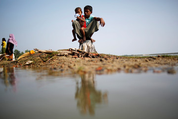 A Rohingya refugee boy holds his brother as he sits on a tree stump after crossing the Bangladesh-Myanmar border, at a port in Teknaf