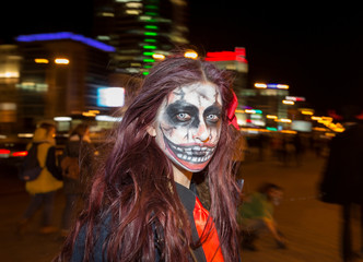 A woman with zombie makeup looks on as she celebrates Halloween in Minsk