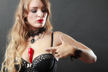 Woman wearing sexy lingerie holding chilli on chest