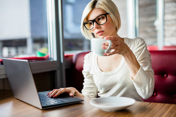 Young Woman Having Coffee While Working On Laptop In Cafe