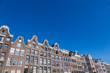 Historical Amsterdam canal houses in a blue sky.