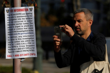 A man stops to photograph an FBI poster asking for assistance near a memorial on West Street two days after a man driving a rented pickup truck mowed down pedestrians and cyclists on a bike path alongside the Hudson River, in New York