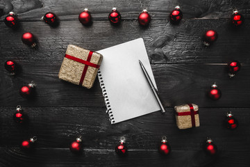 Upper, top, view from above of red evergreen toys, presents, notepad and pen on black background, with space for text writing, greeting.