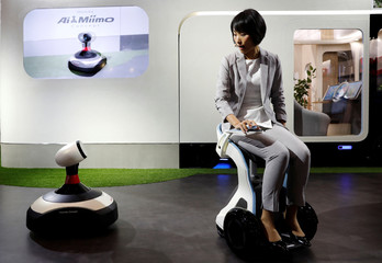 A model riding Honda ChairMobi Concept presents Ai-miimo, Honda's concept model of AI-installed lawn mower, during media preview of the 45th Tokyo Motor Show in Tokyo