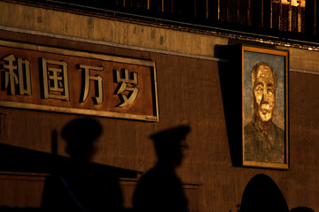 Paramilitary policemen stand guard at sunrise in front of a giant portrait of late Chinese Chairman Mao Zedong at the Tiananmen gate ahead of the visit by U.S. President Donald Trump to Beijing