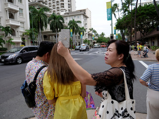 A tourist from Japan takes a picture with her cell phone before she enters a crosswalk in Waikiki, Honolulu, Hawaii.