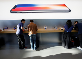 Customers are seen under a picture of Apple's new iPhone X after it goes on sale at the Apple Store in Tokyo