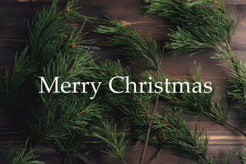 "Pine branches on a wooden background. Christmas tree. Minimal concept. Flat lay, top view. Quote: ""Merry Christmas"""