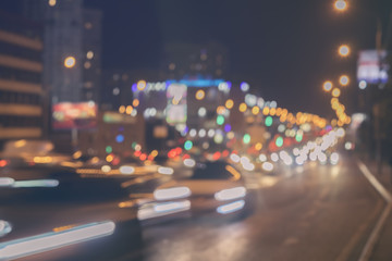 Urban street night traffic with bokeh lights. Blurred auto with bright brake lights, city street lights and speed. Abstract toned blurred background