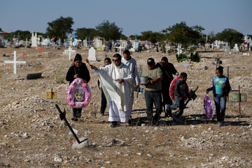 Priest blesses a common grave at San Rafael cemetery during Day of the Dead on the outskirts of Ciudad Juarez, Mexico