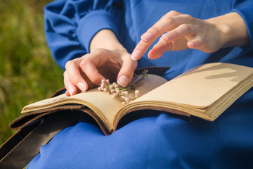 a woman in blue dress wants to dry flowers in a book