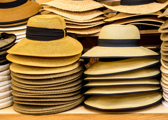 tan colored Panama hats on shelves in a shop