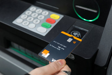 An illustration photo shows an employee of Orange Bank pretending to withdraw money with nfc system without contact at a cash machine outside the Orange Bank headquarters in Montreuil near Paris