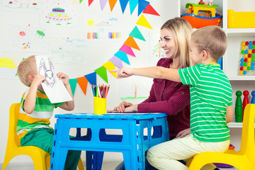Children with mom and draw pictures in the kids room.