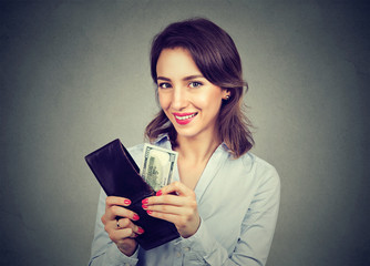 Happy woman taking money out of her wallet isolated on gray background