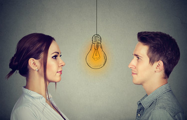 Cognitive skills ability concept, male vs female. Man and woman looking at bright light bulb